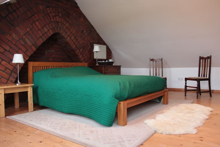 The room is a good size, very light with velux roof windows. The stone chimney arch is a beautiful feature of the room.