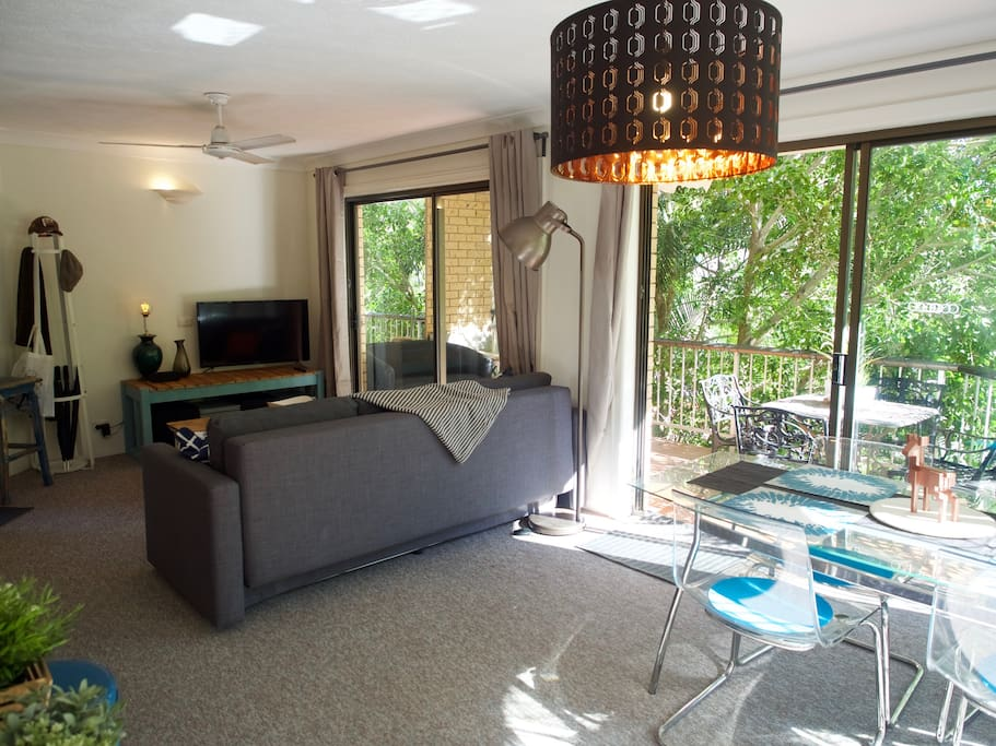 The living room is light, spacious and surrounded by a shaded private balcony.