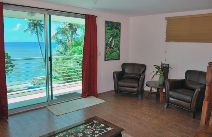 Upstairs bedroom and seating area.  Attached private balcony overlooks the sea.