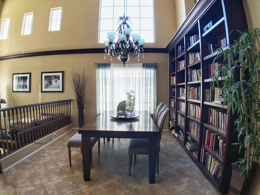 Dining room seats up to 8 and features a grand custom bookshelf with hundreds of books.