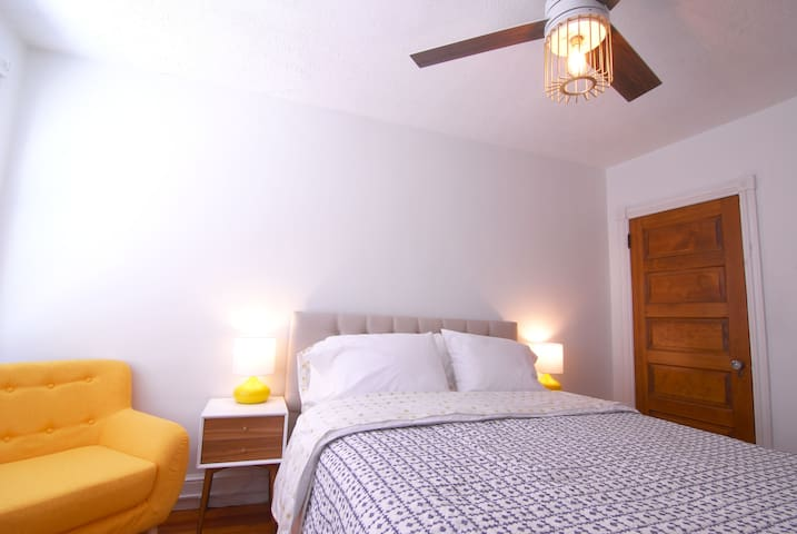 Bedroom 3 with upholstered queen sized bed, top end linens, modern fan lighting.