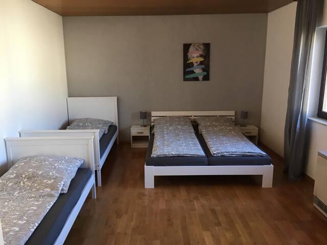 Schlafzimmer mit einem Doppelbett und zwei Einzelbetten
