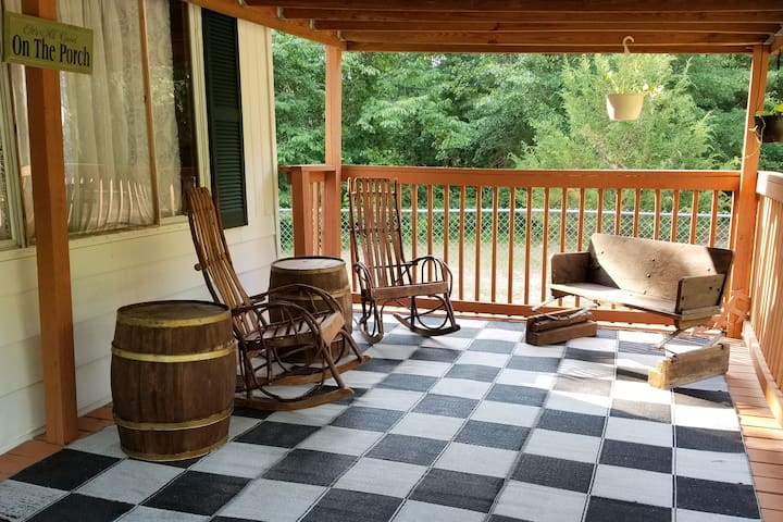 Another view of the front porch captures the antique buggy seat that opposes the rocking chairs.