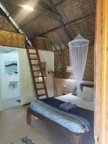 Tarsier cottage  is a  comfortable family room with a upstairs loft. equipped with a comfy double  bed,  queen size bed, and two bunk beds,  seating space inside as well as outside on the veranda overlooking a lush green garden. Private bathroom.