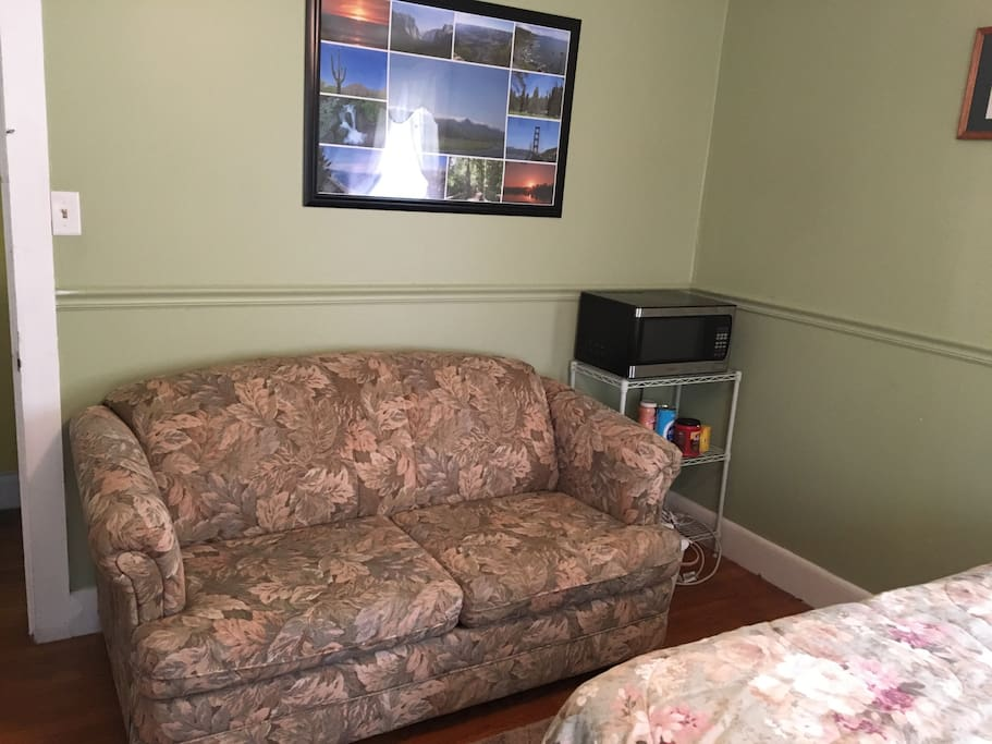 Guest room love seat, microwave and coffee center.