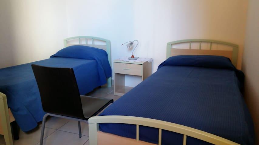 La villetta - zona notte - camera con due letti, comodino centrale e armadio.