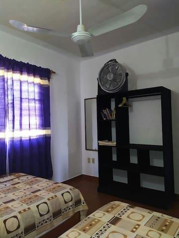 La Habitación cuenta con 2 camas matrimoniales, toallas, jabón para ducha, 2 ventiladores, un mueble para guardar y organizar equipaje, perchero y espejo grande.