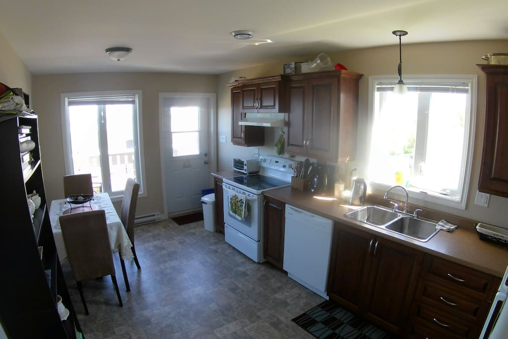large open kitchen gets plenty of light. back patio off the kitchen has a BBQ and breathtaking view of sunsets over conception bay and the islands