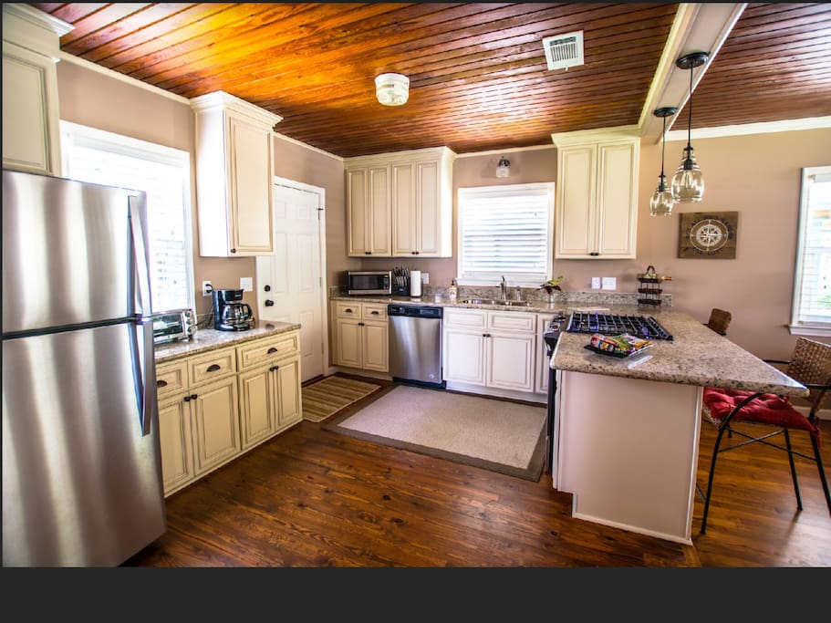 Fully equipped kitchen~ Granite countertops, gas stove, ice maker, microwave, dishwasher, custom soft close cabinets offering lots of storage, pots and pans, crockpot, coffeemaker, etc. The bar area serves as a great work station as well as an eating area.