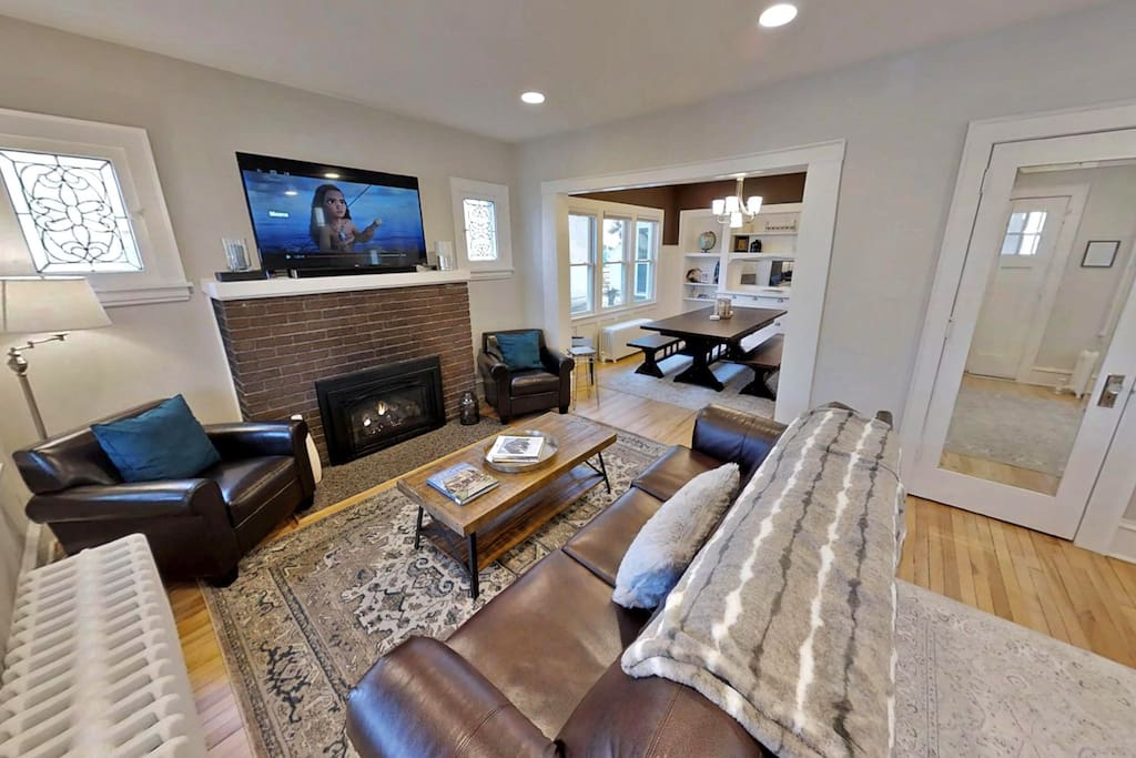Open living area with large screen TV and rustic gas fireplace