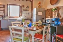 Soggiorno con angolo cottura dotato di stoviglie e accessori cucina. Ampio e moderno piano cottura ad induzione
