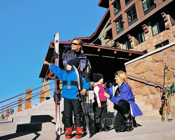 A family with snowboards alongside the resort.
