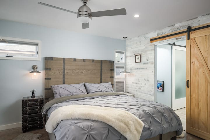 """Master bedroom with large ensuite full master bathroom, king size bed, 50"""" TV with Roku, black out window coverings and ceiling fan"""