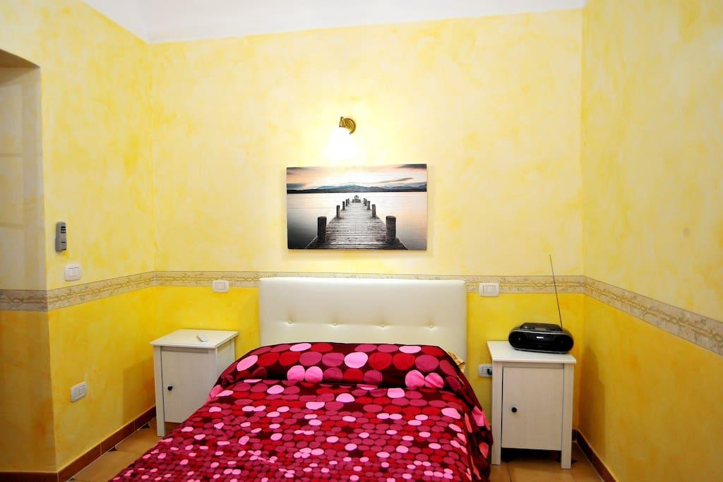 Prima camera da letto composta da letto matrimoniale a 2 posti, comodini, armadio e TV.