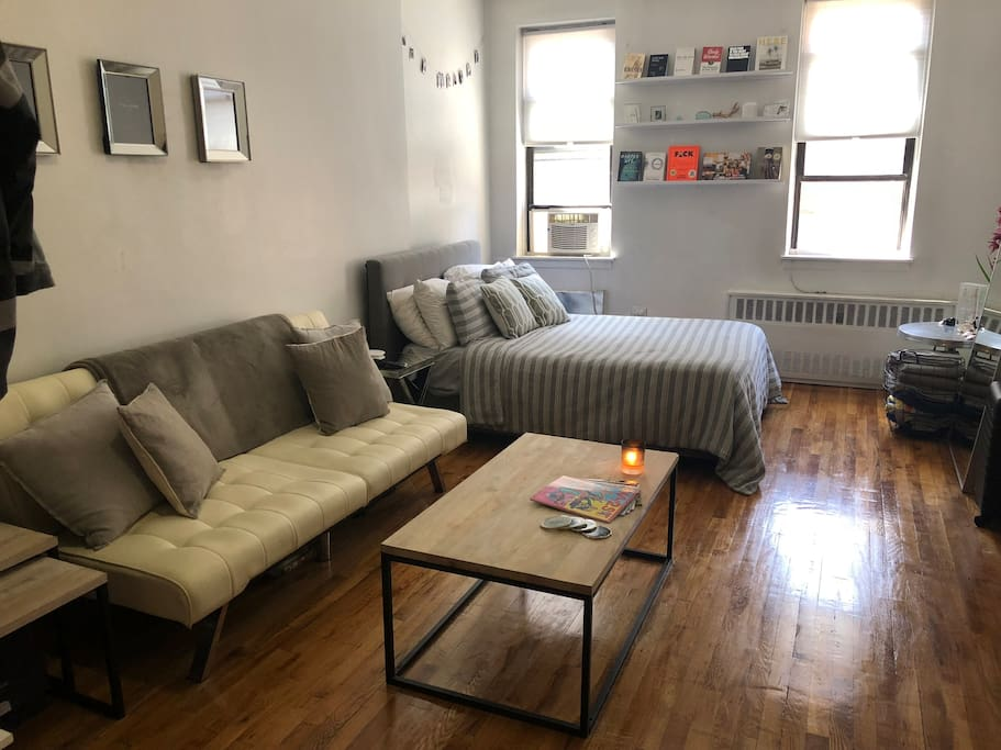 Full view of main studio area - couch, coffee table and full size bed.