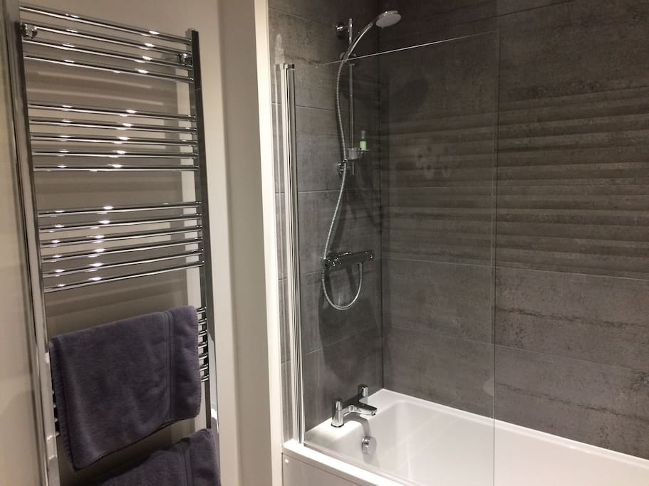 Bathroom with shower over bath and heated towel rail