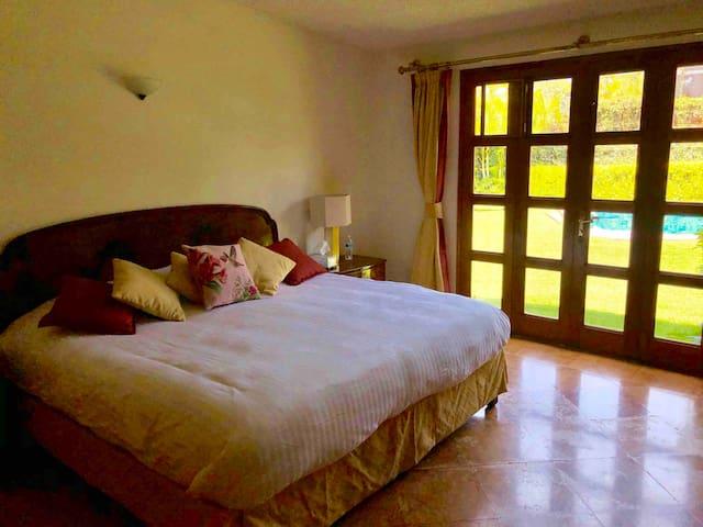 Recámara con cama king size, closet, salida directa hacia el jardín y baño completo enfrente