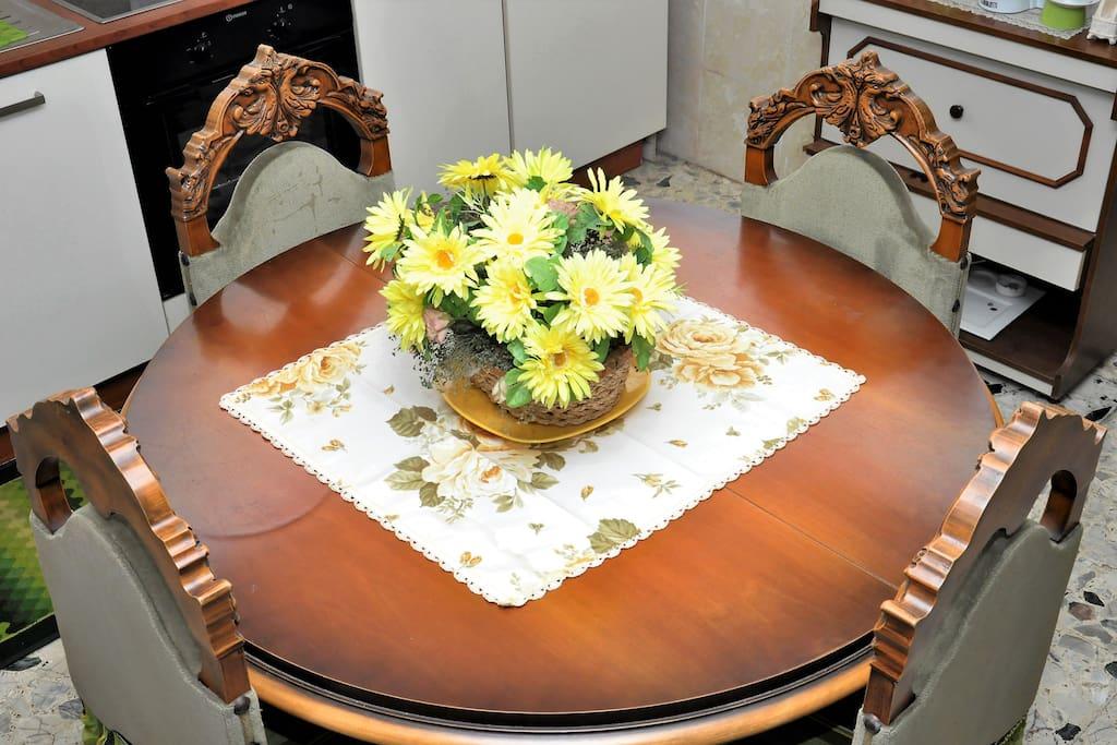 Tavola rotonda e sedie in legno massiccio con decorazioni a intaglio