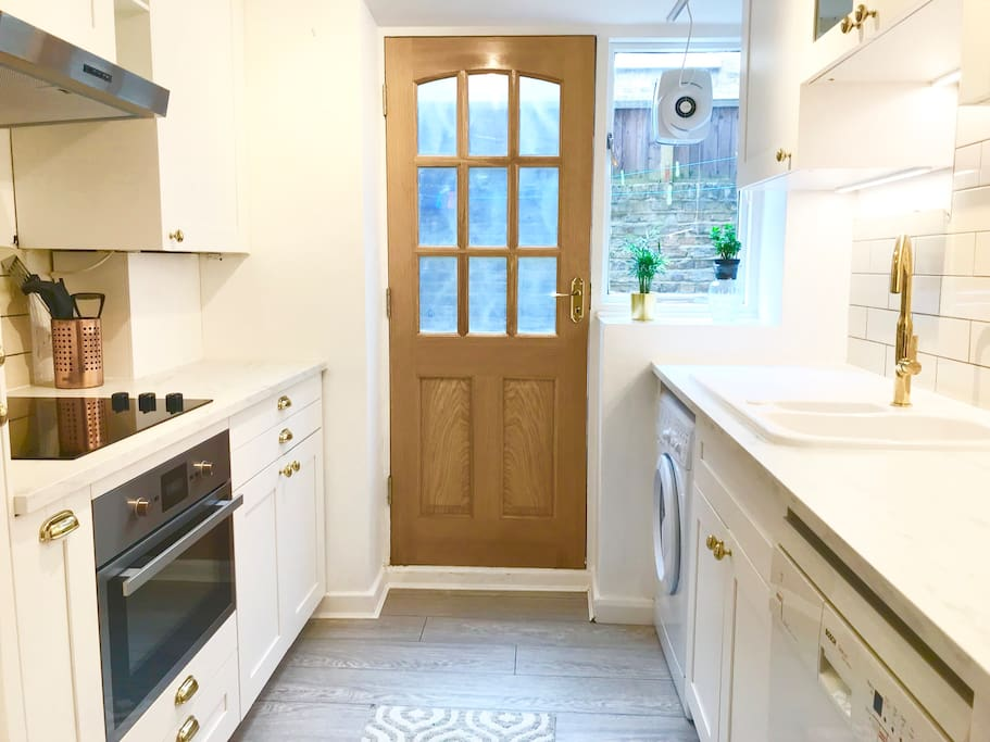 Brand new trendy kitchen features marble worktops, grey wood flooring and fresh white cabinets with brass fittings with the door opening into the garden