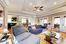 Hardwood floors gleam in the living room, furnished with a sleeper sofa and collection of lovely chairs.