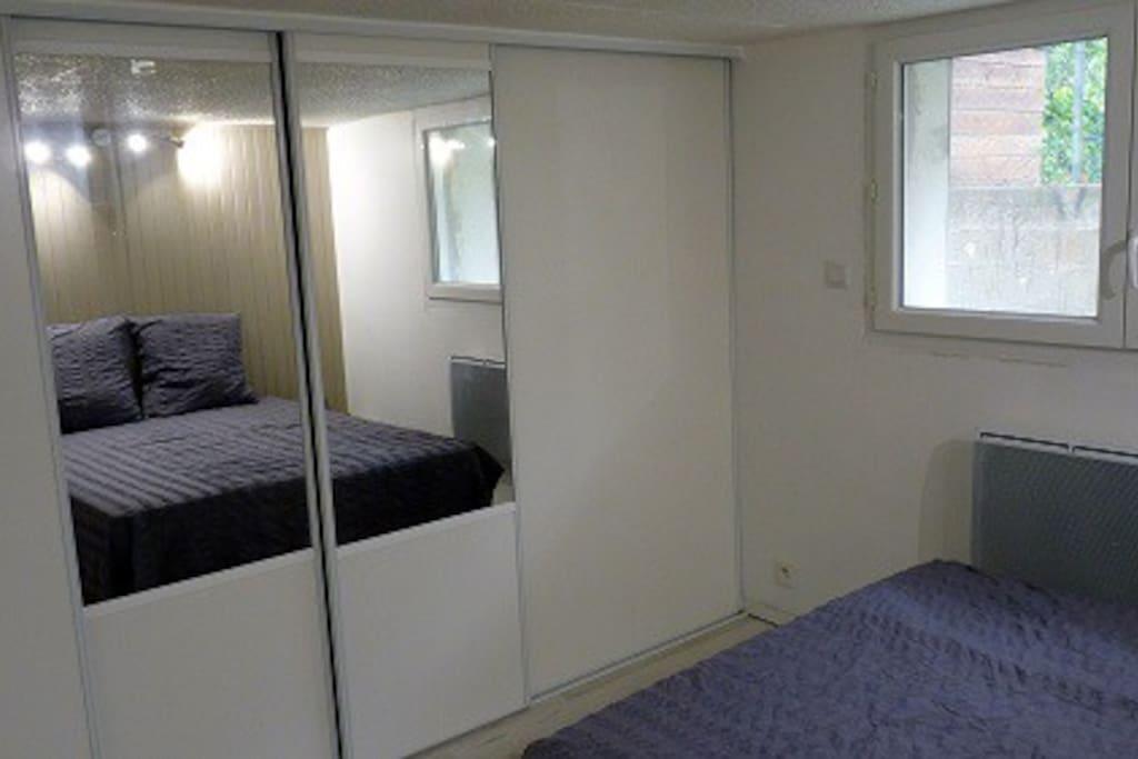 Chambre lit de 140 avec dressing 4 portes coulissantes comprenant : T V 82 cm, penderie, étagères
