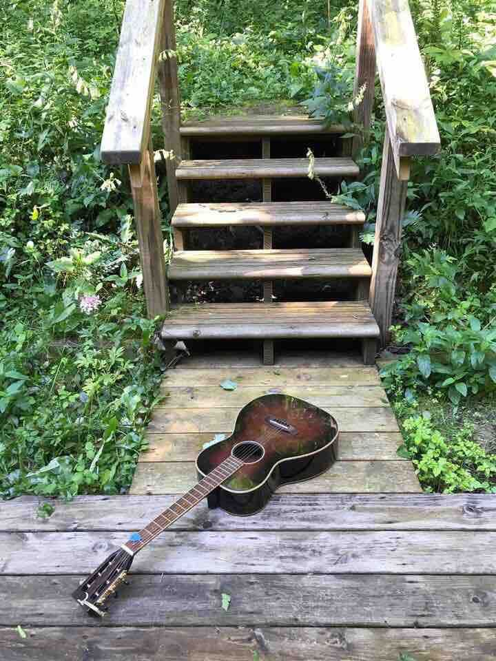 I heard guitar music floating through the trees.