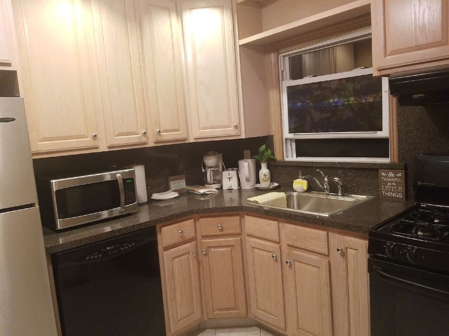 Kitchen area with coffee maker, kettle, toaster.