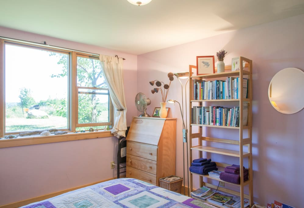 A desk/dresser and bookcase full of local magazines, resources, and ecologically-minded books are features of the Lavender Room.