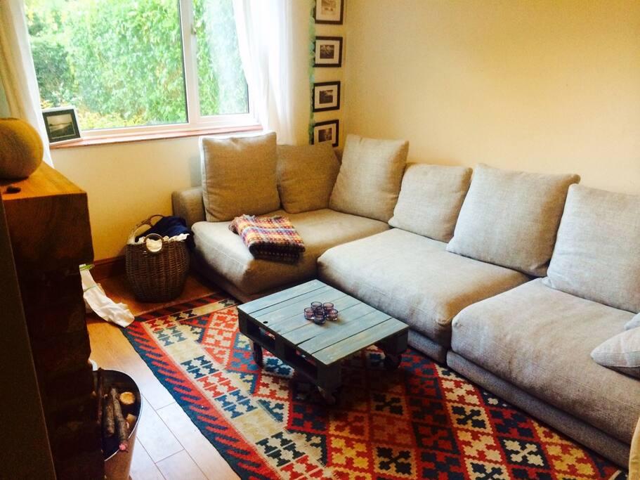 Snug living room with huge sofa & wood burner