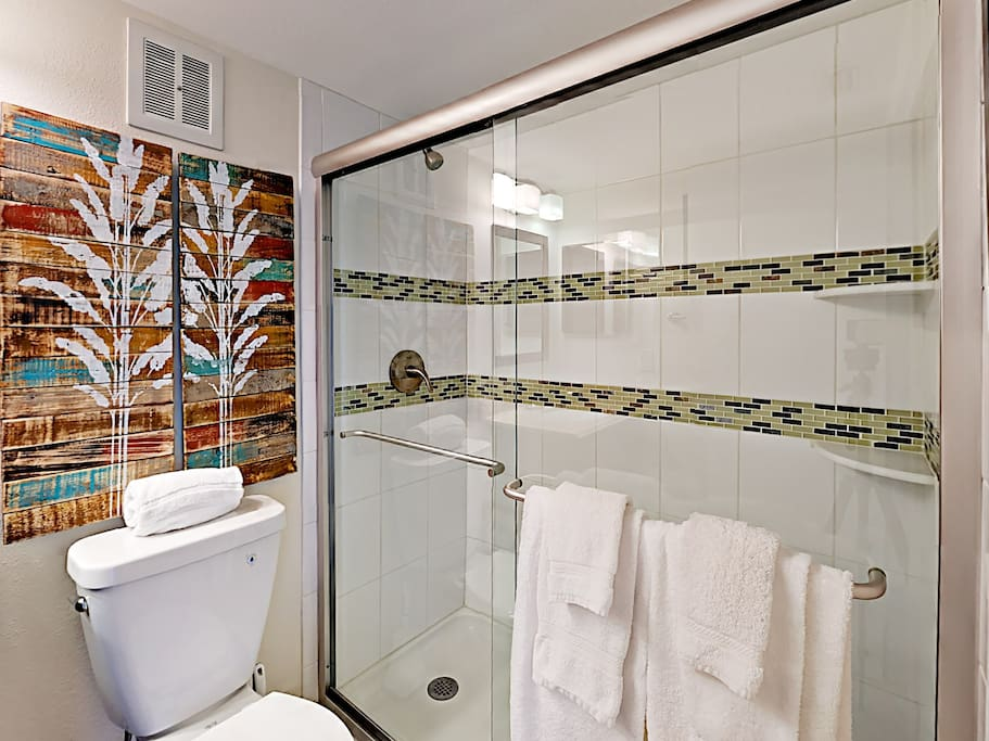 The walk-in shower features decorative tile work.