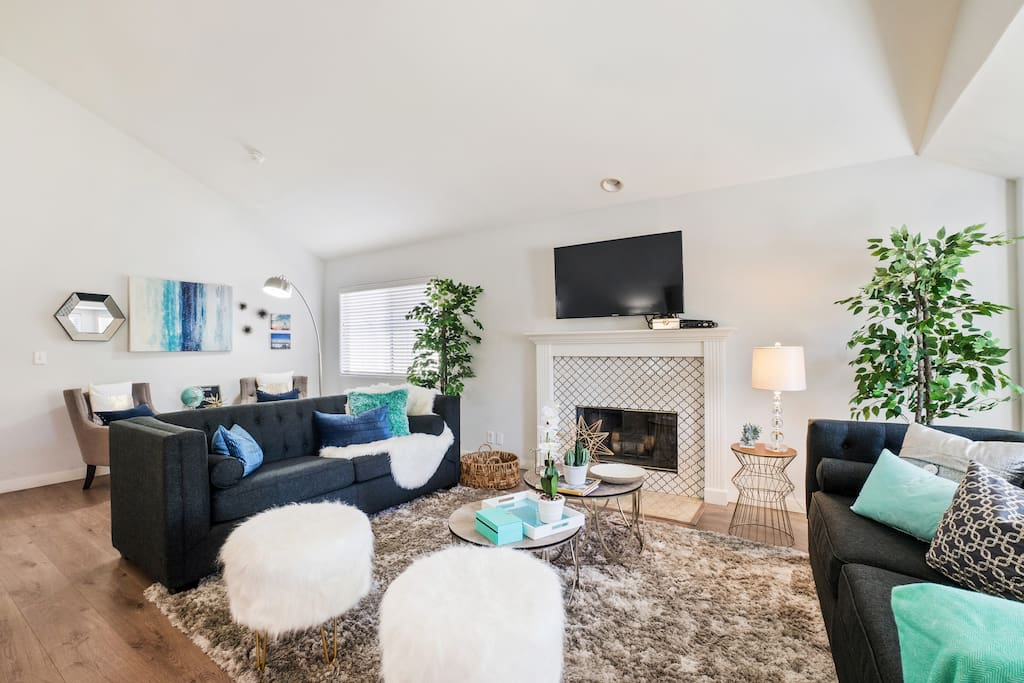 Living- family room featuring 60 inch smart TV and three seating areas.