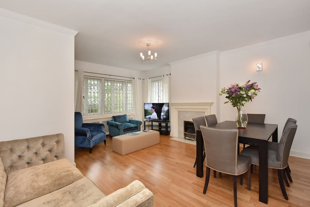 The bright, spacious Lounge and dining area with large, flat screen TV and fireplace