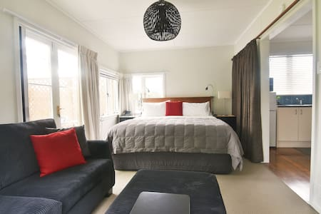 The living space features a super king size bed, lounge, TV and seperate kitchenette and bathroom. French doors lead to the covered outdoor living space, and views over the tropical gardens.  The cottage is serviced daily.