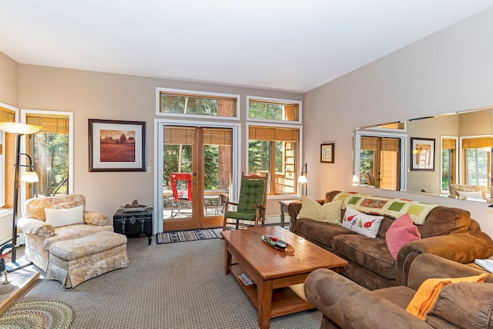 Open and bright living space with LED TV, stone hearth and gas fireplace