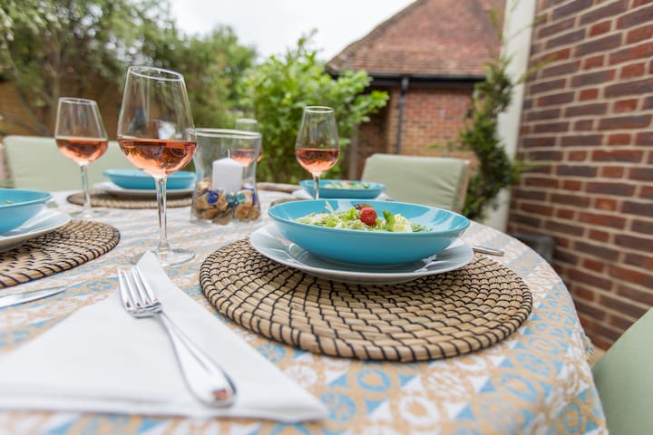 Alfresco dining on patio with views of sea in distance