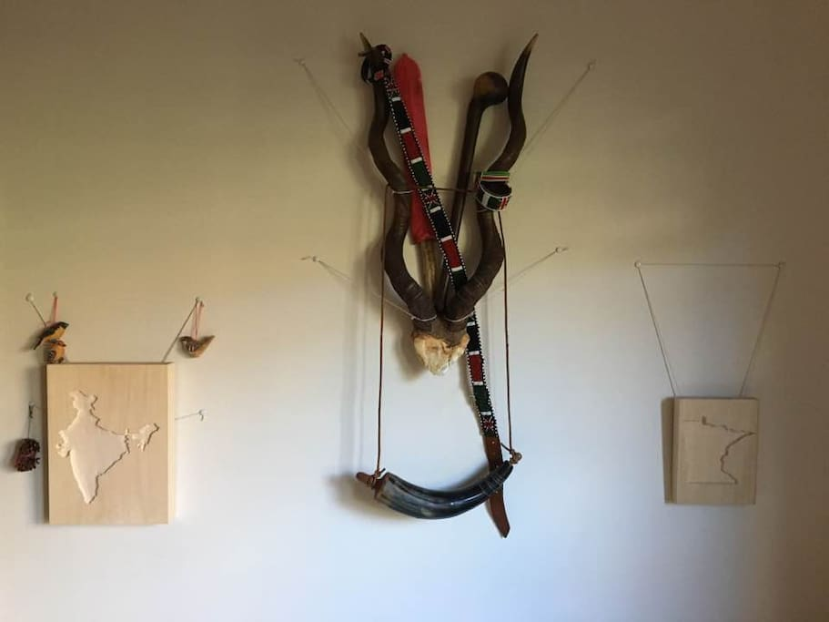 My wood carvings of India and Minnesota respectively, some gazelle antlers, bracelets, a belt, machete and club from Kenya, and a replica voyageur's gunpowder casket.
