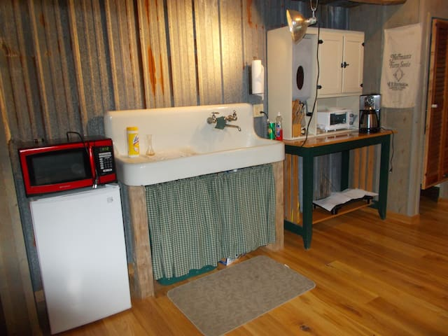 Small kitchen area, with coffee pot, micro, and frig., also electric frying pan.