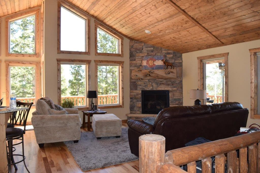 The spacious great room has comfy seating, a gas fireplace and high vaulted ceilings with floor-to-ceiling windows.