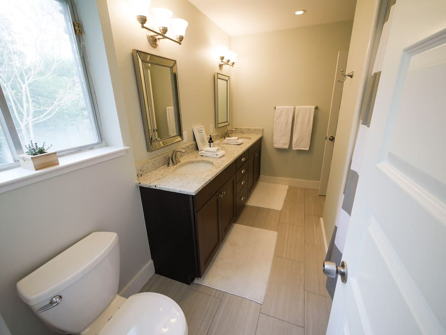 Huge bathroom with double sinks and plenty of plush white linens.