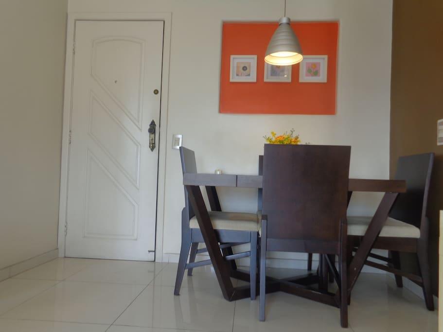 Mesa de jantar com cadeiras estofadas.