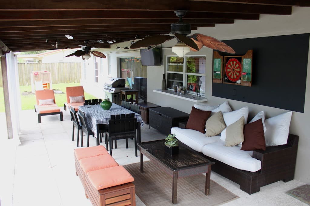 Full view of patio including dartboard and yard space with bocce, croquet.