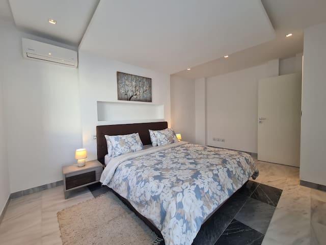 Chambre 2 avec un lit King size et un grand dressing donnâtes accès sur une terrasse à l'étage