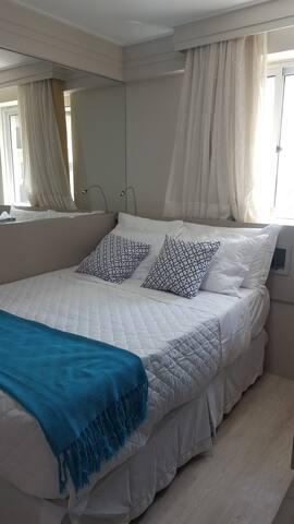 Quarto com cama de casal, ar condicionado, tv,  guarda-roupa.