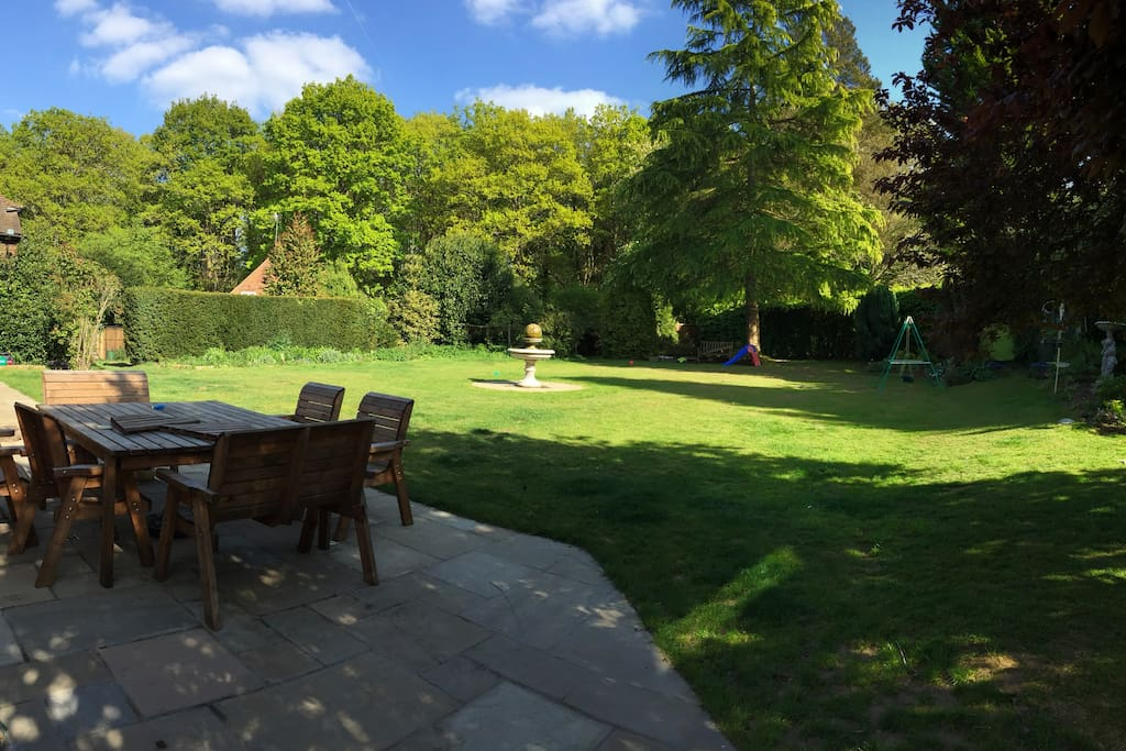 The house is surrounded by an acre of garden with a large table for eating.