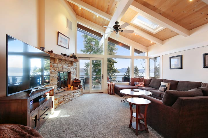 Main living room with wood burning fireplace, large flat screen tv, and very large sectional couch.  Amazing lake views