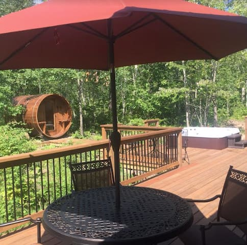 Outdoor barrel sauna and hot tub on a deck off the back of the house.