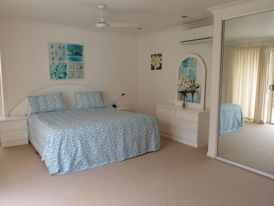 King sized bed with ensuite and view of pool, with flat screen TV on wall.
