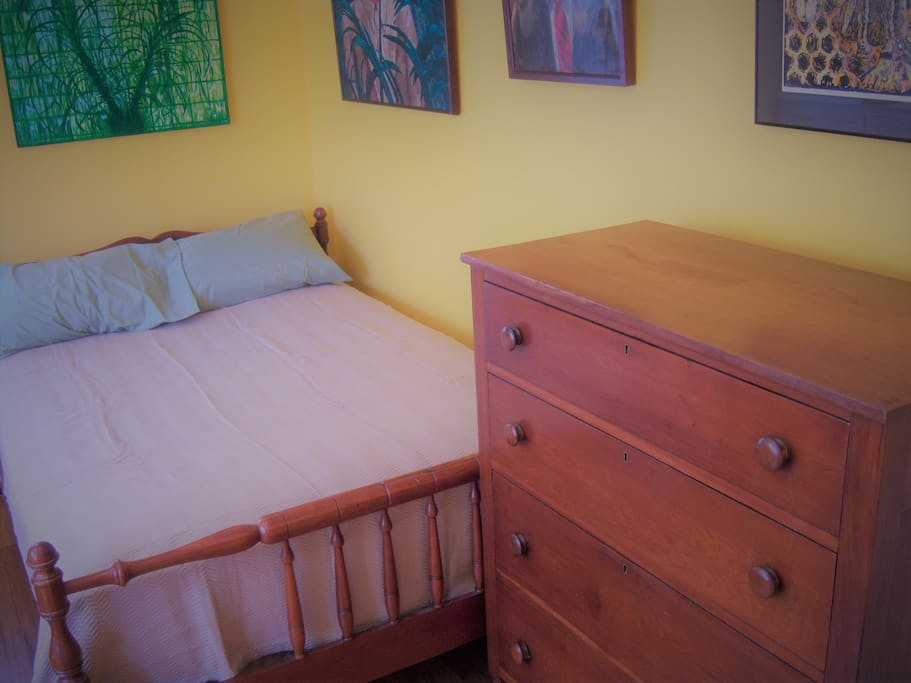 The private bedroom has a queen sized bed and a chest of drawers.