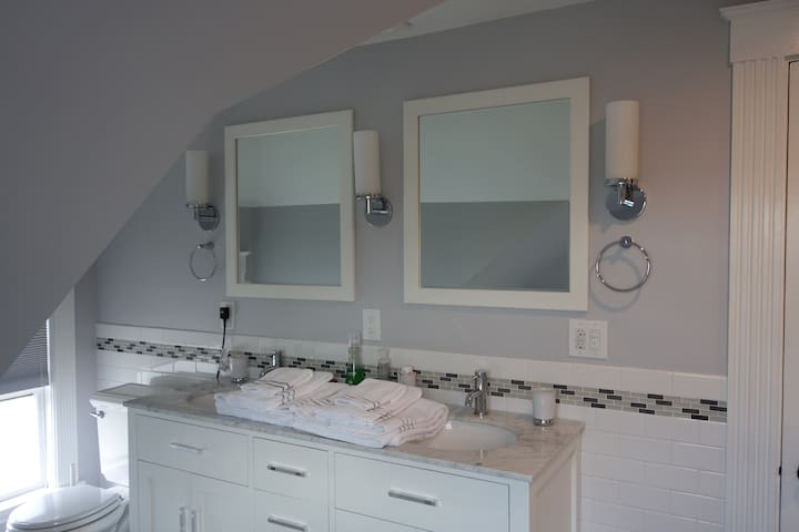 Double vanity sink with marble countertops, lights, and mirrors. Natural light from the skylight as well.