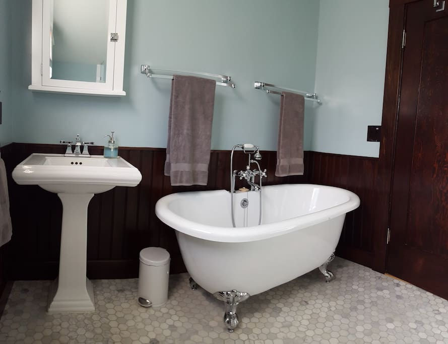 Recently renovated private bathroom with a large shower, claw-foot tub and marble floor.
